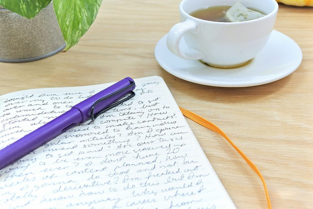 writing in a rhodiarama with a purple lamy safari while drinking tea