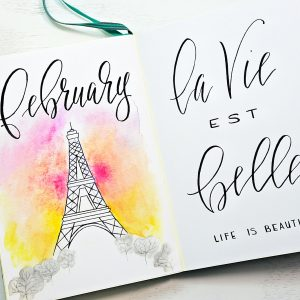 Eiffel tower themed Bullet journal cover page and hand-lettered quote for February.