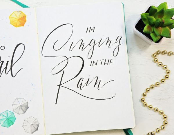 Singing in the rain hand lettered quote for a bullet journal.